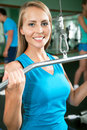 Woman at the gym fitness doing arms exercises on a machine Stock Photo