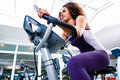 Woman in gym spinning on fitness bike Royalty Free Stock Photo