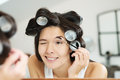 Woman in hair curlers applying eye makeup the bathroom mirror contouring her eyebrows with eyeliner Royalty Free Stock Photo