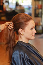 Woman hair styling a young having her long styled in ponytail a salon Stock Image