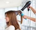 Woman at the hairdresser beautiful blow drying her hair Royalty Free Stock Photography
