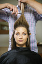 Woman in hairdresser shop cutting long hair female client happy about and looking at camera Royalty Free Stock Image