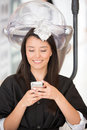 Woman at the hairdresser texting on her cell phone Stock Images