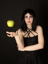 Woman with halloween make up sthrowing green apple Royalty Free Stock Photos