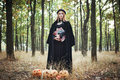 Woman in halloween witch costume in forest Royalty Free Stock Photo