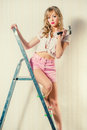 Woman with hammer sexy blonde a and ladder indoors Royalty Free Stock Photography