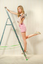 Woman with hammer sexy blonde a and ladder indoors Royalty Free Stock Photo
