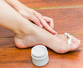 Woman hand applying moisturizer in her feet best way to hydrate the skin a Royalty Free Stock Photo