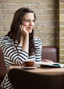 Woman with hand on chin looking away in coffeeshop thoughtful young Royalty Free Stock Photos