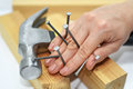 Woman hand with hammer and nails. Royalty Free Stock Photo