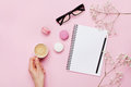 Woman hand hold cup of coffee, cake macaron, clean notebook, eyeglasses and flower on pink table from above. Female working desk.