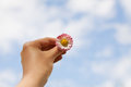 Woman hand holding a Daisy against of the blue sky with clouds, freedom, peace, hope, trust and purity Royalty Free Stock Photo
