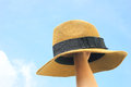 Woman hand holding panama hat with sky blue Stock Images