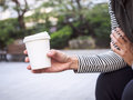 Woman hand holding paper cup of coffee in park outdoor hipster Stock Images