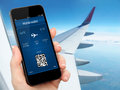 Woman hand holding the phone with mobile wallet and plane ticket against background of window blue sky airplane Royalty Free Stock Photo