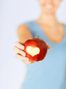 Woman hand holding red apple with heart shape