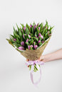 Woman hand holding soft lilac tulips flowers on white background. bouquet decorated with kraft paper Royalty Free Stock Photo