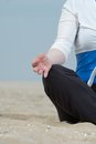 Woman hand in lotus yoga pose at the beach closeup of Stock Photos