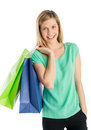 Woman with hand in pocket carrying shopping bags portrait of happy young against white background Royalty Free Stock Images
