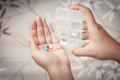 Woman hand pouring pills from a pill reminder box Royalty Free Stock Photo