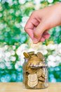 Woman hand put gold coin money in the glass jar on table in gard Royalty Free Stock Photo
