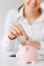 Woman hand putting coin into small piggy bank Stock Photography