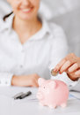 Woman hand putting coin into small piggy bank business office household school tax and education concept Stock Photo