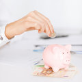 Woman hand putting coin into small piggy bank business office household school tax and education concept Royalty Free Stock Images