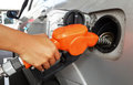 Woman hand refilling gas to car with fuel on a filling station Stock Images