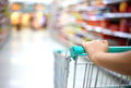 Woman hand with shopping cart in supermarket Royalty Free Stock Photos