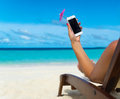 Woman hand showing mobile phone and cocktail umbrella on the sky Royalty Free Stock Photo