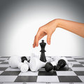 Woman hand touching king figure on chess board Royalty Free Stock Photo