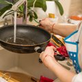 Woman hand washing frying pan close up under running water. Hand cleaning. Royalty Free Stock Photo