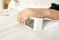 Woman hand on white digital alarm clock in bedroom Royalty Free Stock Photo