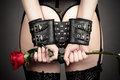 Woman in handcuffs holding a rose his hand Royalty Free Stock Image