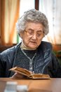 Woman with hands holding bible elderly caucasian as she reads Royalty Free Stock Image