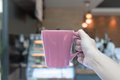 Woman hands holding coffee cup with blurred coffee shop