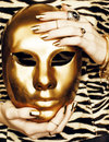 Woman hands holding golden carnival halloween mask, rich luxury manicure and jewelry close up on zebra print, fashion Royalty Free Stock Photo
