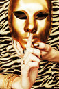 Woman hands holding golden carnival mask, rich luxury manicure and jewelry close up on zebra print Royalty Free Stock Photo