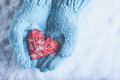 Woman hands in light teal knitted mittens are holding beautiful a entwined vintage red heart on snow love st valentine concept Royalty Free Stock Photos