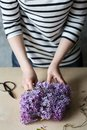 Woman hands making bouquet of lilac in a pot on the table