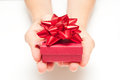 Woman hands with present giving in red ribbon box Stock Images