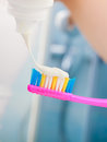 Woman hands putting toothpaste on toothbrush Royalty Free Stock Photo