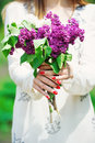 Woman hands with red manicure holding bunch of lilac flowers delicate spring bouquet Royalty Free Stock Photos