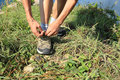 Woman hands tying shoelace on seaside mountian grass Royalty Free Stock Photos