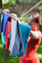 Woman hanging clothes on laundry line in garden Royalty Free Stock Photo