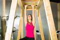 Woman hanging at high or horizontal bar is and training her arms Royalty Free Stock Photos