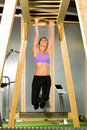Woman hanging at high or horizontal bar is and training her arms Stock Photo
