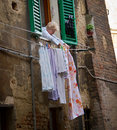 Woman hanging laundry italy a pins clean on a clothesline outside her window in siena Royalty Free Stock Images