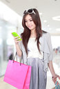 Woman happy with mobile phone and shopping bags Royalty Free Stock Photo